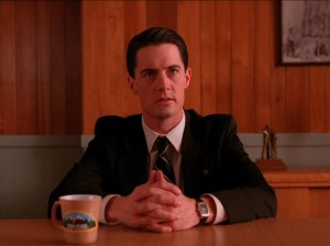 Agent Dale Cooper sitting with cup of coffee
