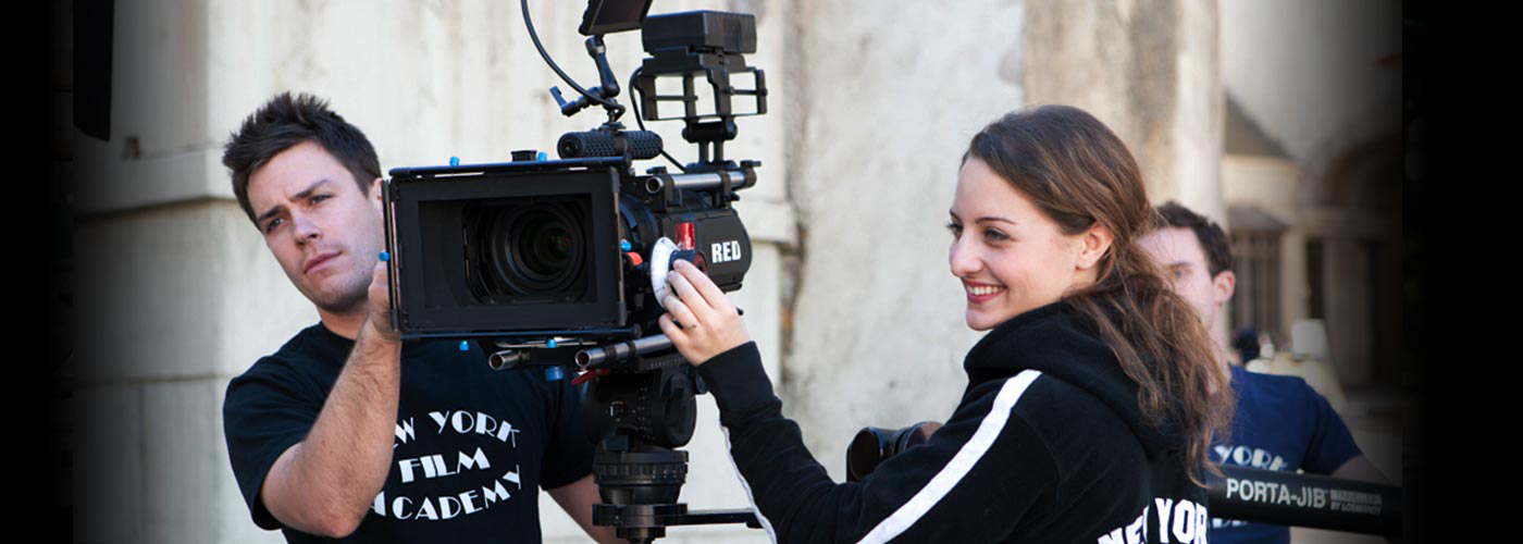 NYFA filmmaking student smiles while working with her classmates to operate a RED camera on location on the Universal Studios backlot.