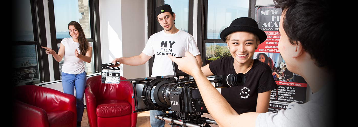 New York Film Academy student in bowler hat smiles at director as her fellow crewmembers prepare for a shot at the LA campus.