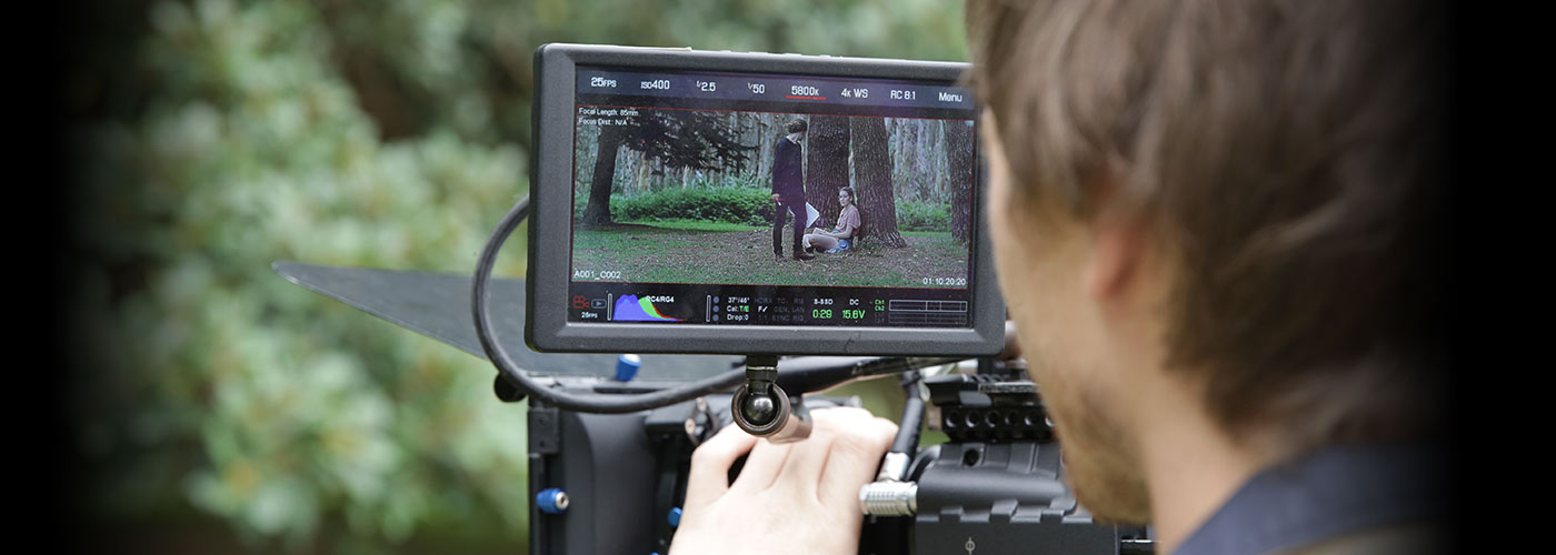 Over-the-shoulder view as a New York Film Academy student director inspects the outdoor forest scene in his camera monitor.