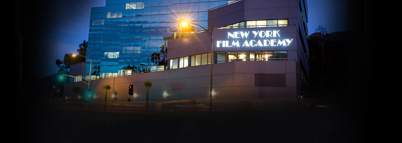 A night shot of the New York Film Academy Los Angeles building, with pink clouds above.