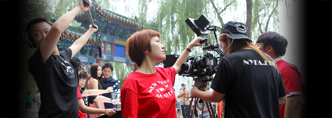 woman in red shirt holds camera while man holds microphone