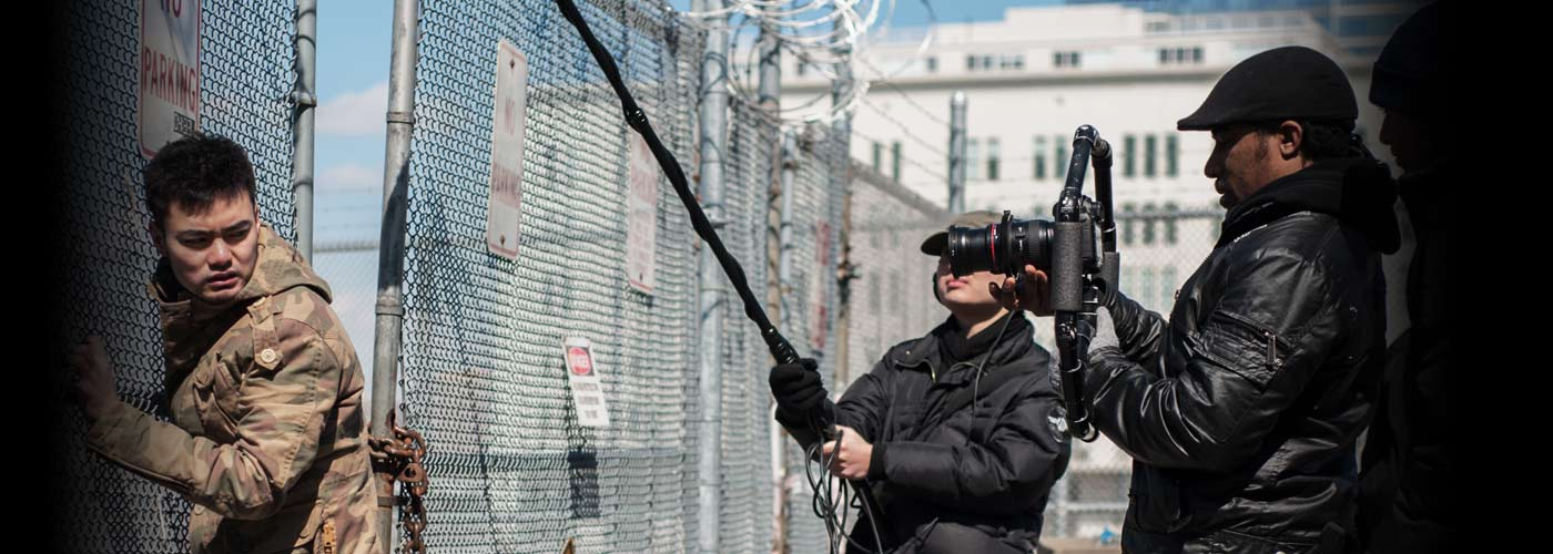 New York Film Academy acting student performs intense scene by chainlink fence.