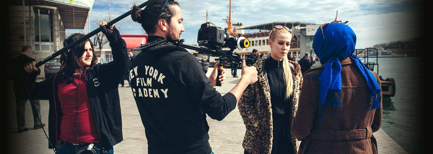 NYFA filmmakers capture the performances of an acting for film student in a leopard print coat and a classmate in a hijab on a pier near a ferry.