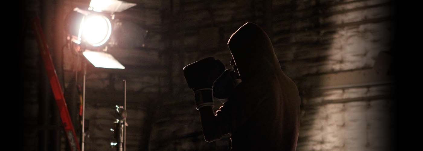 New York Film Academy acting student performing in boxing globes on set.