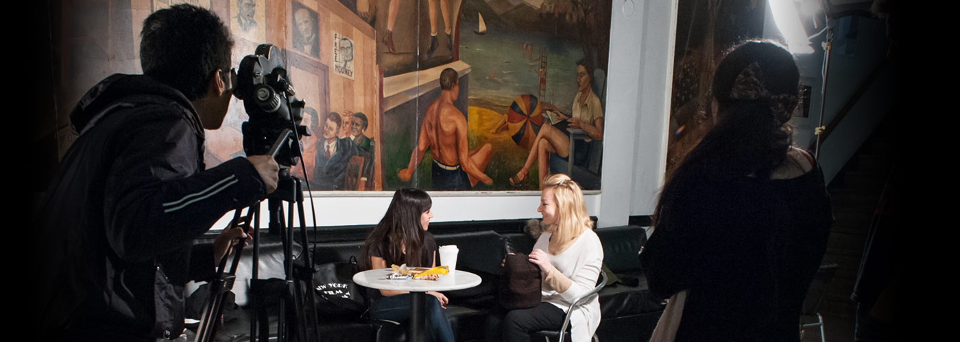 New York Film Academy acting students perform on a couch under a large painting of sunbathers.