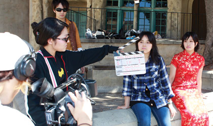 A NYFA student slates as a young Asian acting students in a red dress and a blue plaid shirt poise for