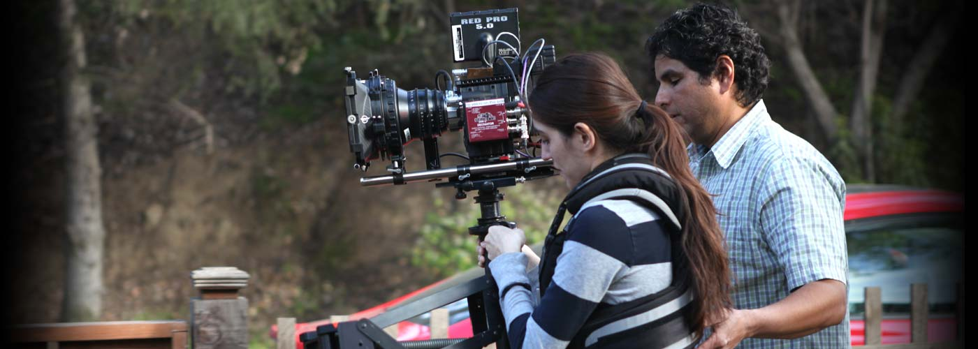 A NYFA instructor helps a student operate a RED digital camera