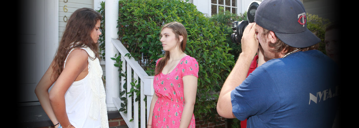 Student with handheld camera films two actresses outside home