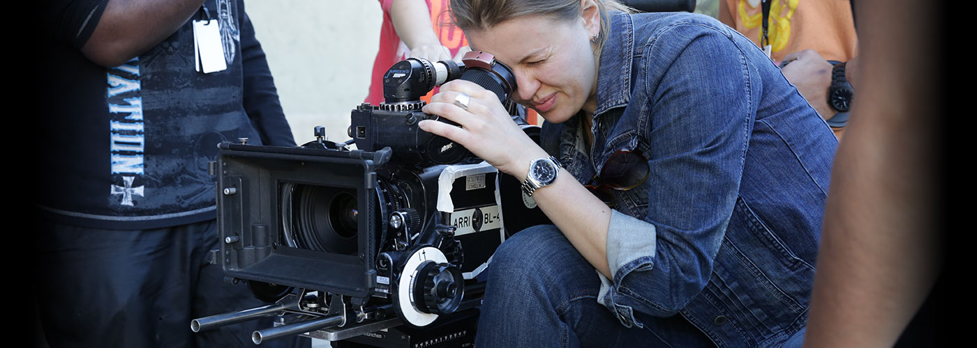 A NYFA student in a denim shirt focuses on a scene with a camera.