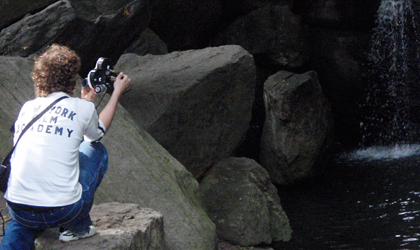A student films a waterfall while standing on rocks
