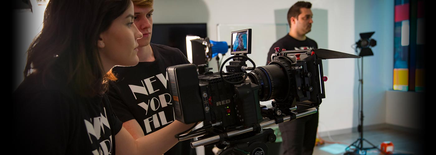 Film school students observe a scene through a RED camera