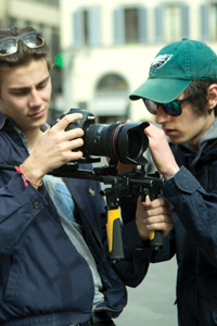 A NYFA student cinematographer in a windbreaker holds the camera while the student director in a green hat works with him to set up a shot.