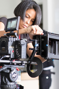 A NYFA student with a bob haircut concentrates as she adjusts the settings on her RED camera during a project shoot.