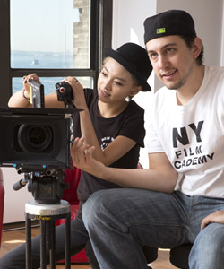 A NYFA student in a bowler hat adjusts her RED camera while her classmate watches the scene they are framing.