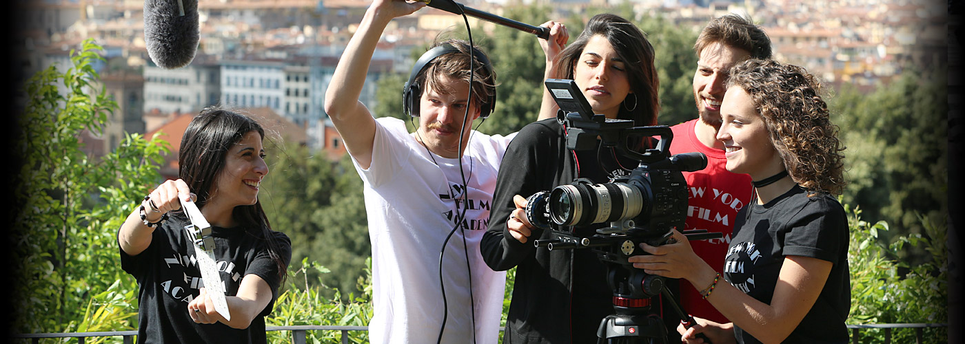 A NYFA Florence student crew of three women and two men slates for a sunny outdoor shot overlooking the city.