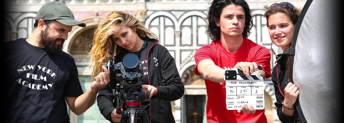 Three NYFA student crew members prepare to film an acting student with long blonde hair as she walks along a flowered path in Florence.