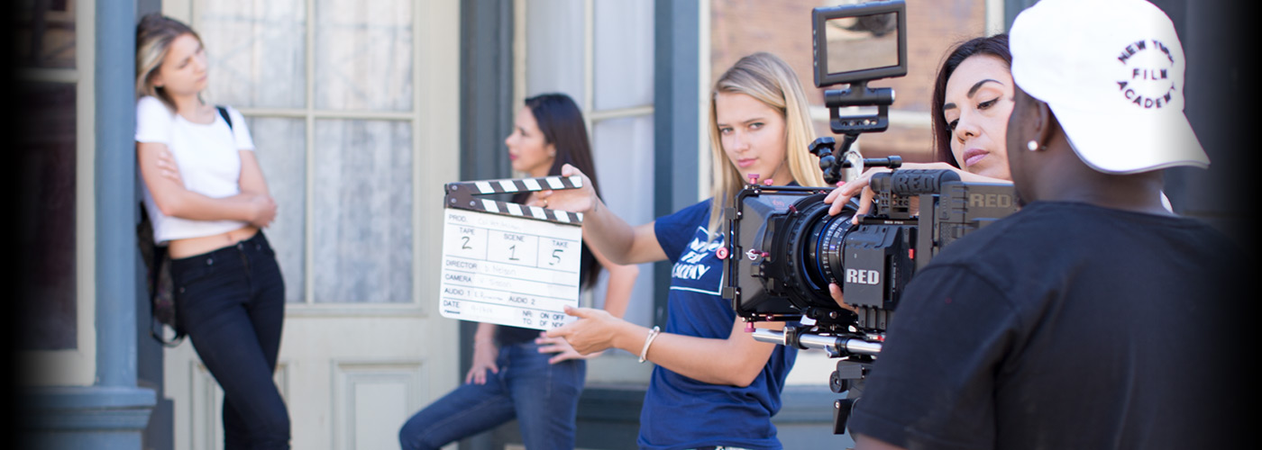 Two young woman and a young man form a NYFA student film crew, slating as they prepare to film two young actresses performing on the Universal Studios backlot.