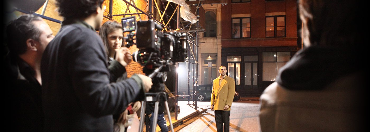 A NYFA acting for film student in a yellow blazer performs an outdoor night scene as a student crew films.