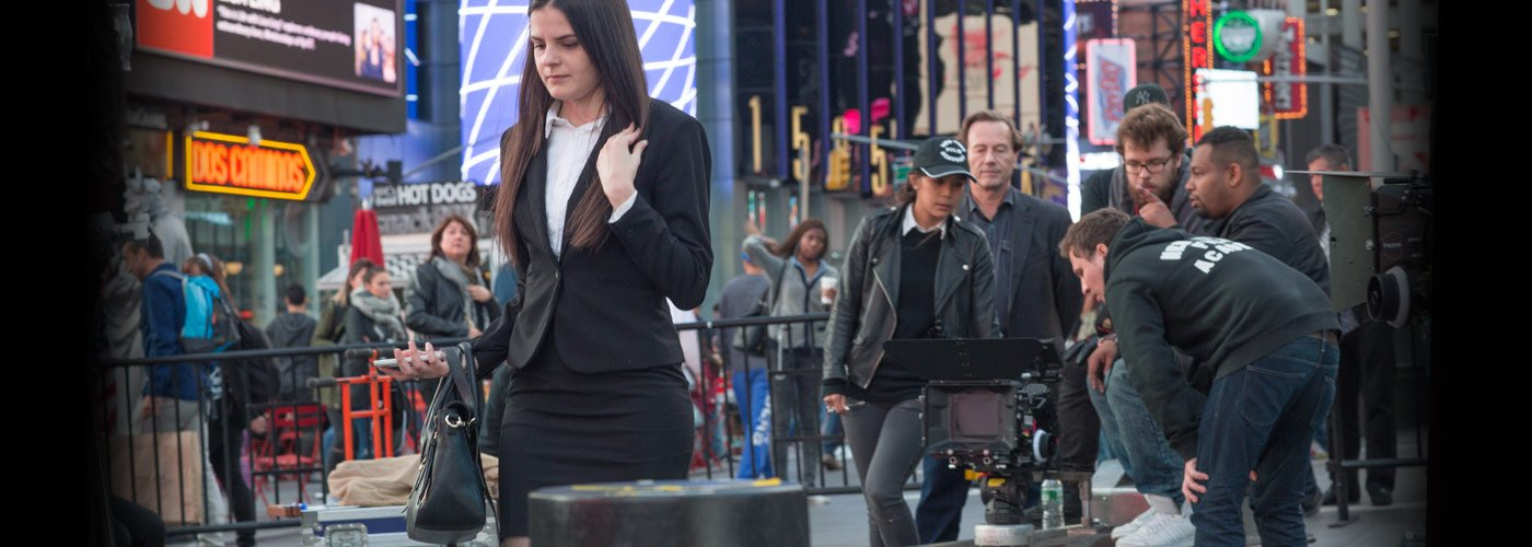 A NYFA acting student in a business skirt suit walks through Times Square as a student crew captures the bustling scene.