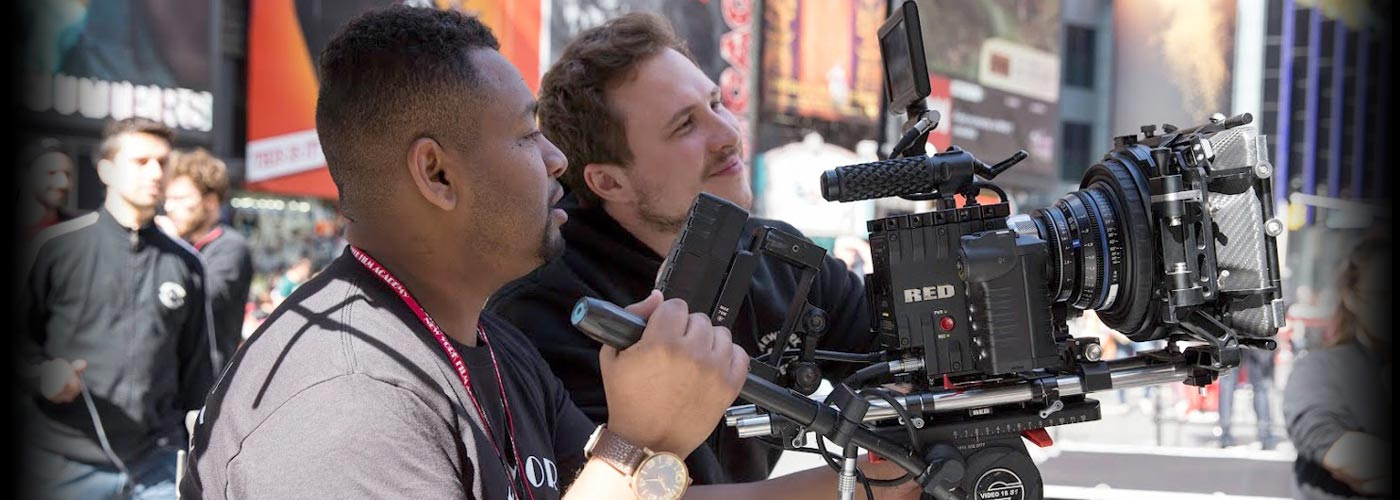 Two NYFA filmmaking students in t-shirts work together to operate a RED camera in Times Square as their classmates look on.