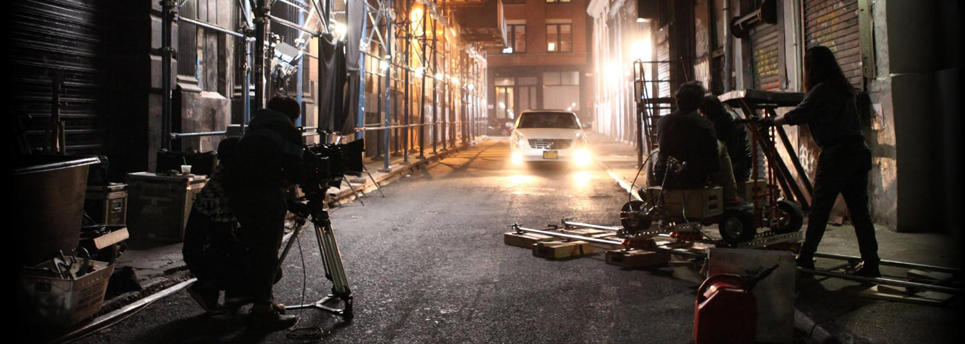 NYFA filmmaking students work to capture a track shot of a dramatically lit car in a back alley.
