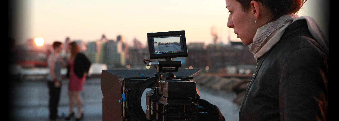 A NYFA filmmaking student studies the monitor of her camera as she films two acting students performing a scene on a NYC rooftop.