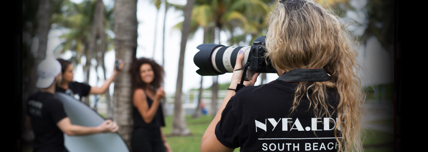 New York FIlm Academy photography student with wavy hair shoots a model under palm trees on location in South Beach, Miami.