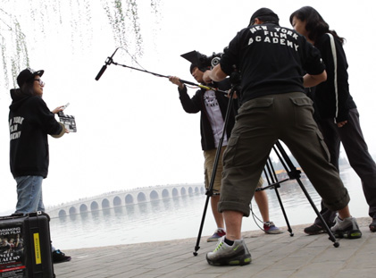 Students film by the water in Shanghai, China