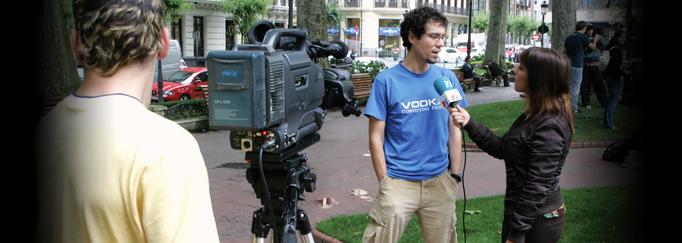 Broadcast journalism student interviews a subject outdoors