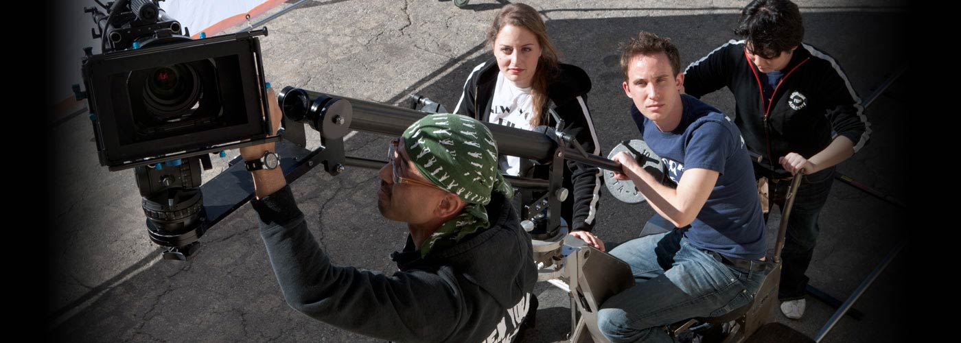Producing students adjust a camera on set