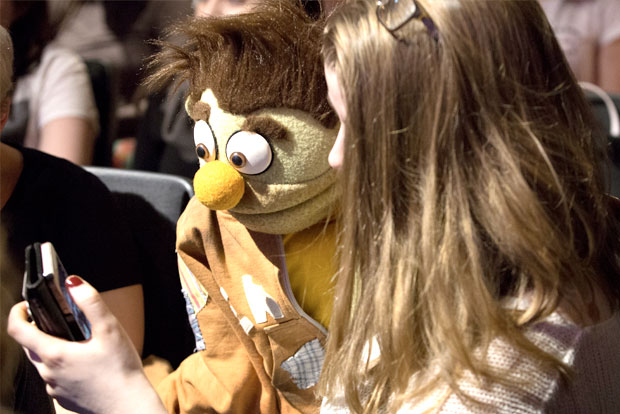 A student taking a selfie with a puppet at the Jeff Marx event