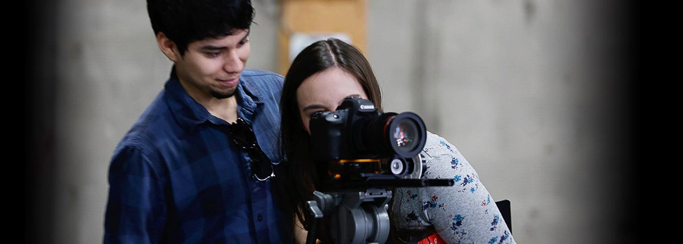 A NYFA filmmaking student in blue plaid shirt smiles and watches his classmate as she films through a Canon camera on a tripod.