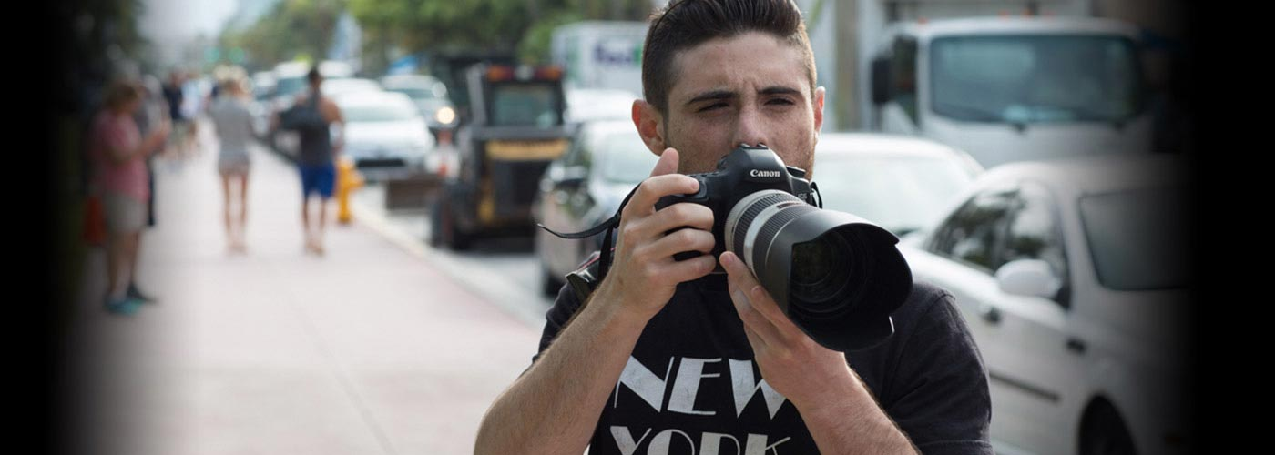 A NYFA photography student on an outdoor sidewalk squints as he peers above his camera to plan his next shot.