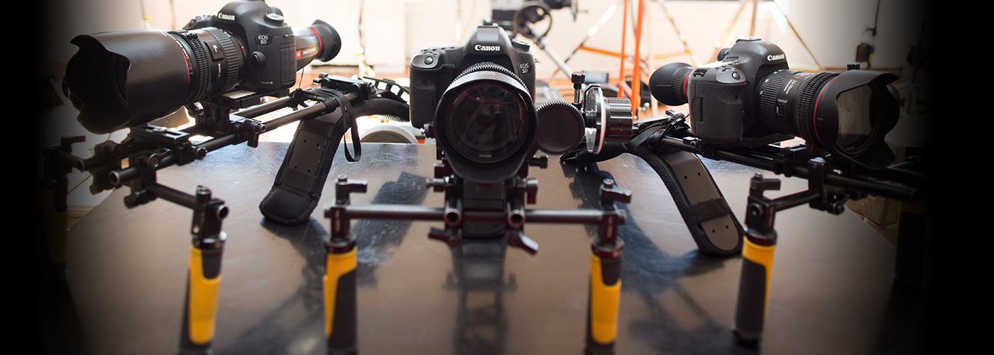 Three canon HD cameras rest on steadicam mounts on a steel table, with a brightly lit NYFA studio space visible in the background.