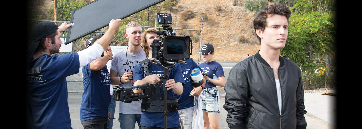 A NYFA student in a black windbreaker is filmed by a crew of six AFA filmmaking students on an outdoor set.