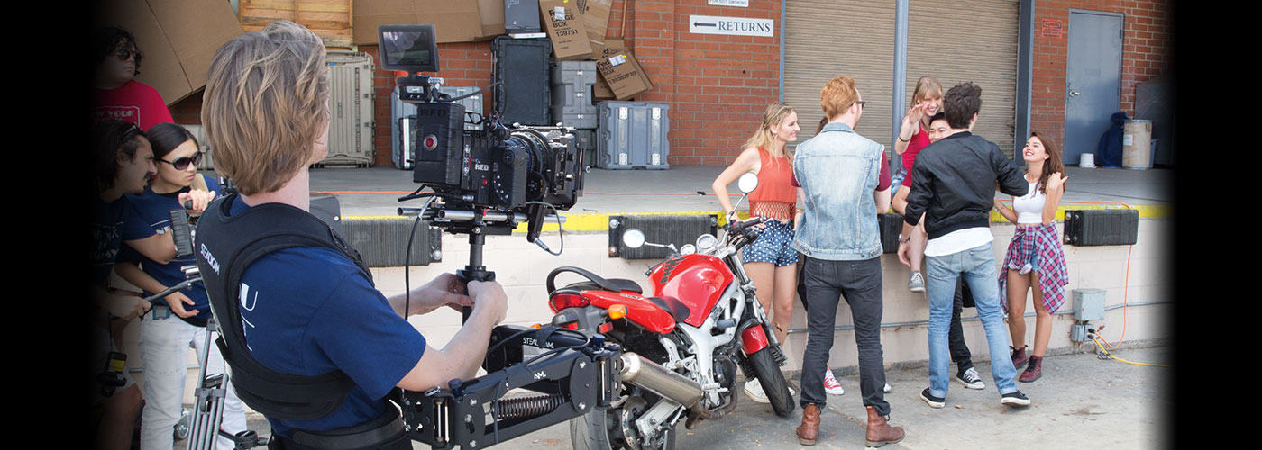 A NYFA AFA student wearing a steadicam films a group of six acting for film students by a red motorcycle.