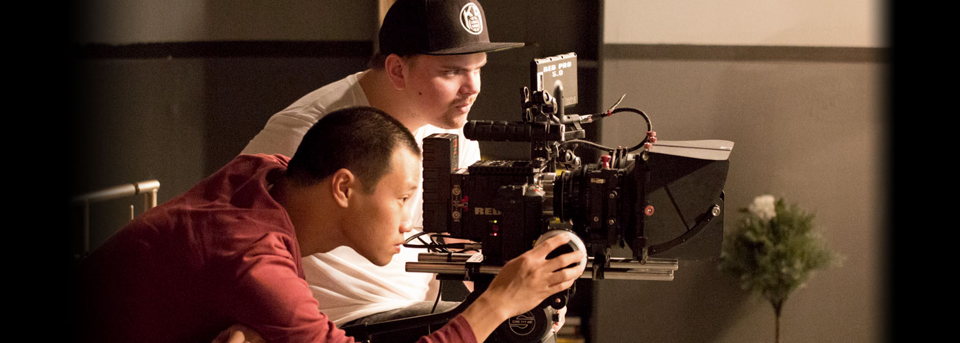Two male NYFA AFA filmmaking students concentrate with their RED camera while filming an indoor scene.