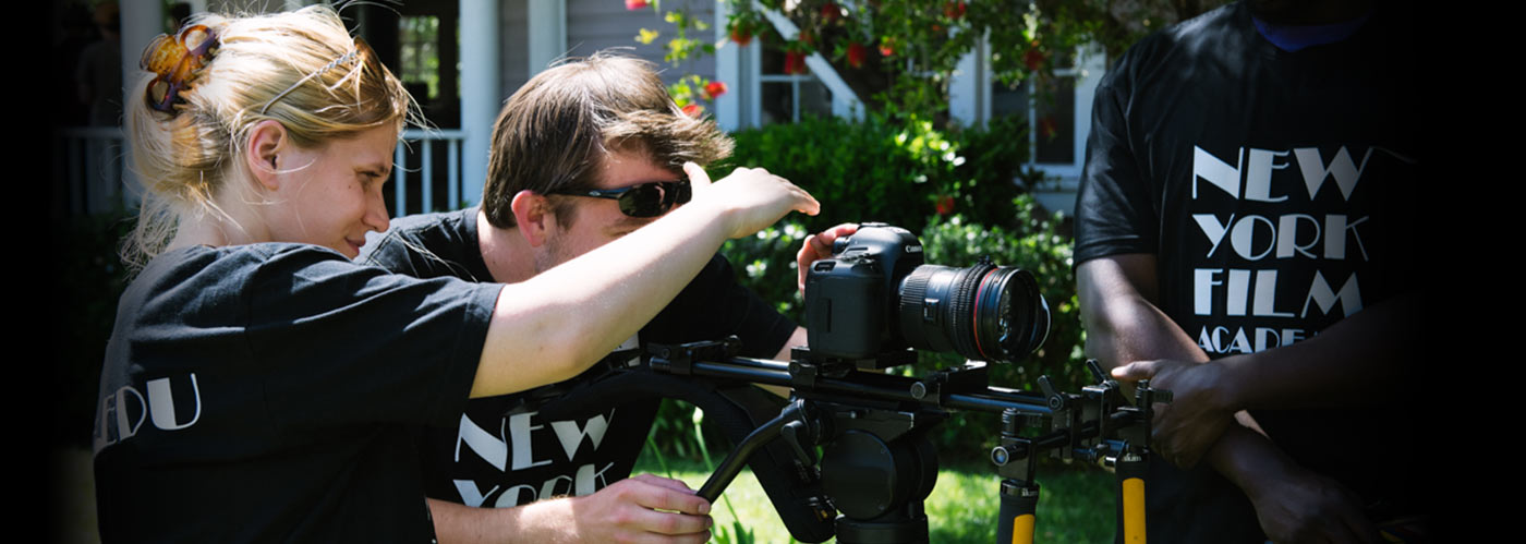 A NYFA filmmaking student in a grey and yellow hoodie concentrates as he frames a shot with his Canon camera.
