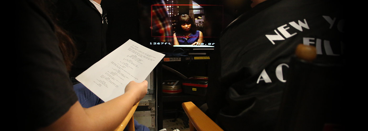 An over-the-shoulder view of two NYFA screenwriting students, one in a NYFA jacket and one holding the pages of a script, as they watch the monitor during filming of a scene they wrote.