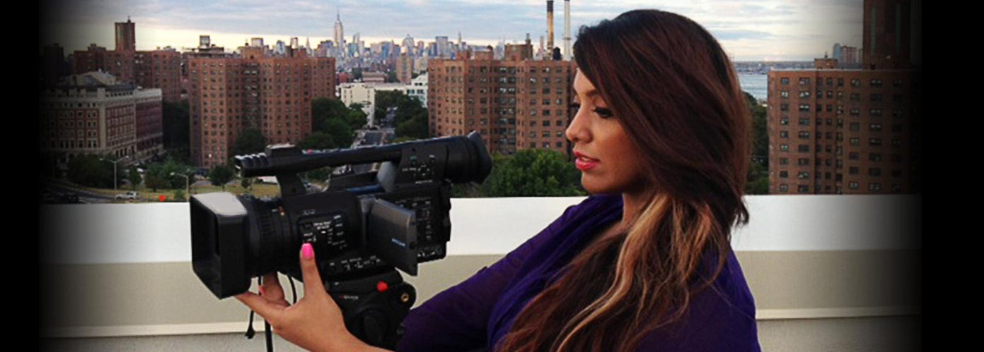 A NYFA broadcast journalism student works with her camera to produce a segment on a New York City rooftop.