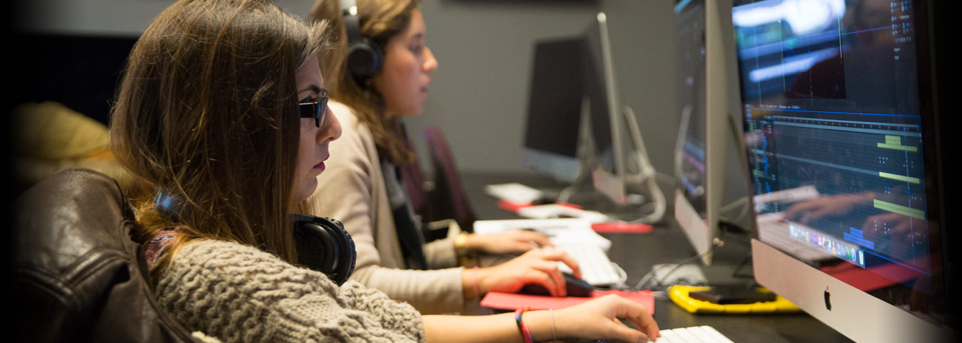 A NYFA digital editing student in glasses and a tan sweater concentrates while working on her project in class.