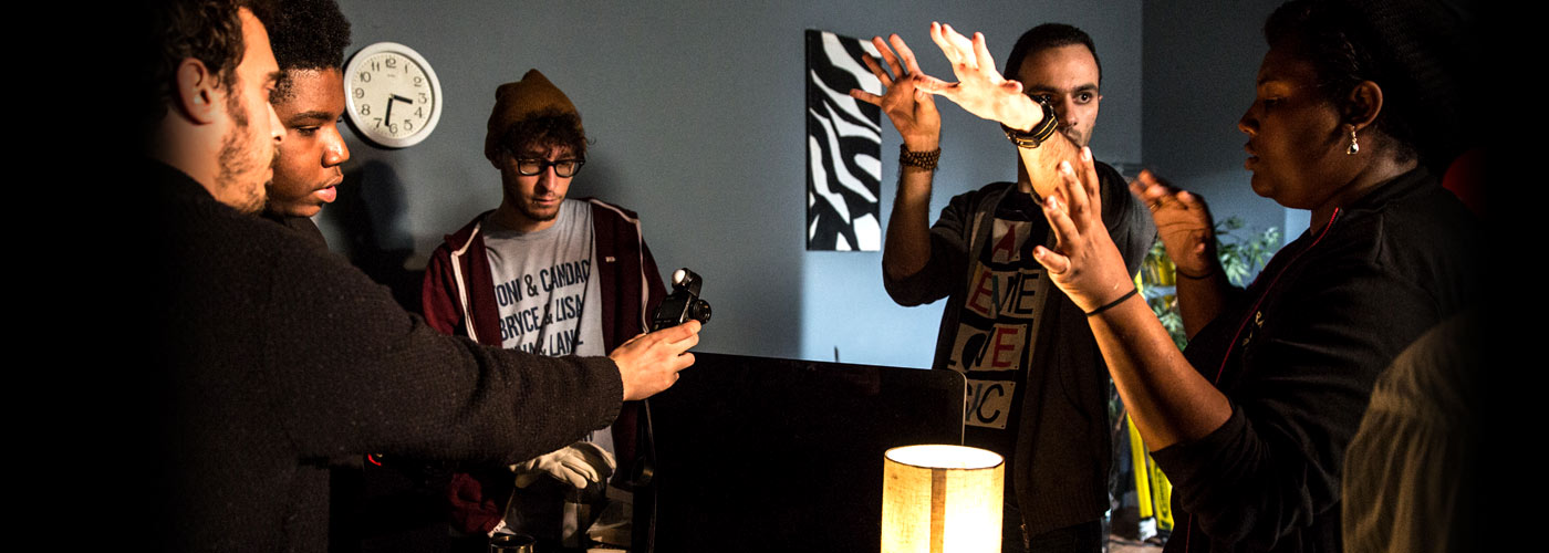 NYFA directing students in a grey room with a clock on the wall work together to plan a shot.