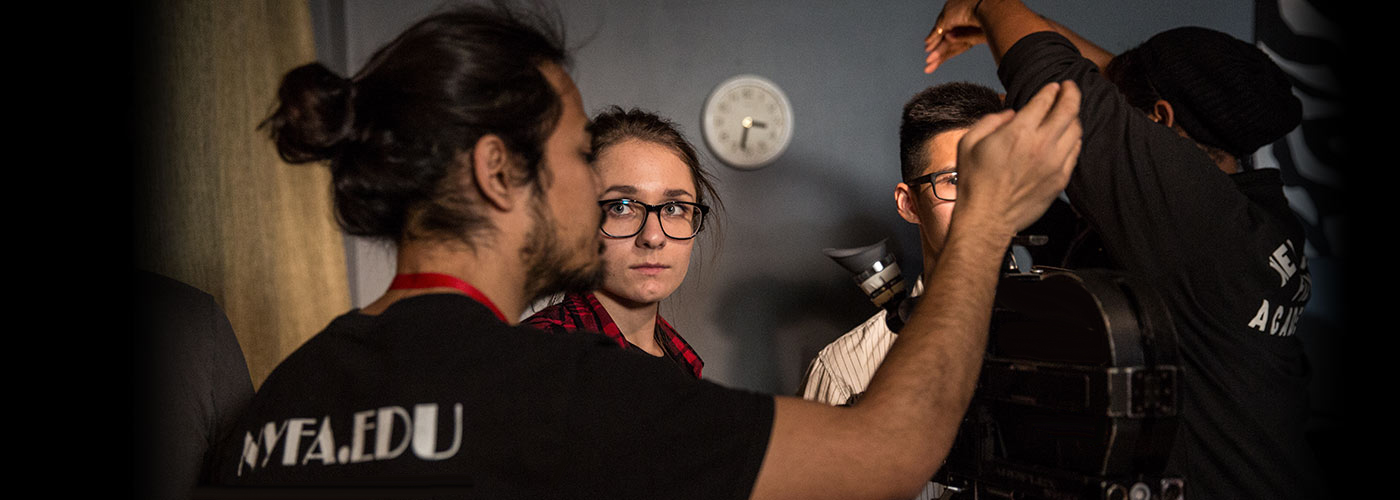 A NYFA directing student in glasses watches as her classmate with a beard adjusts the camera.