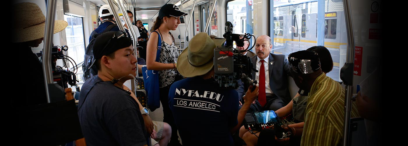 New York Film Academy documentary filmmaking students film a man in a suit in a train car.