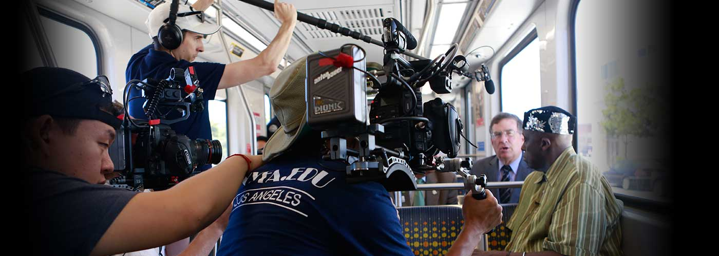 New York Film Academy documentary filmmaking students film passengers inside a train car.
