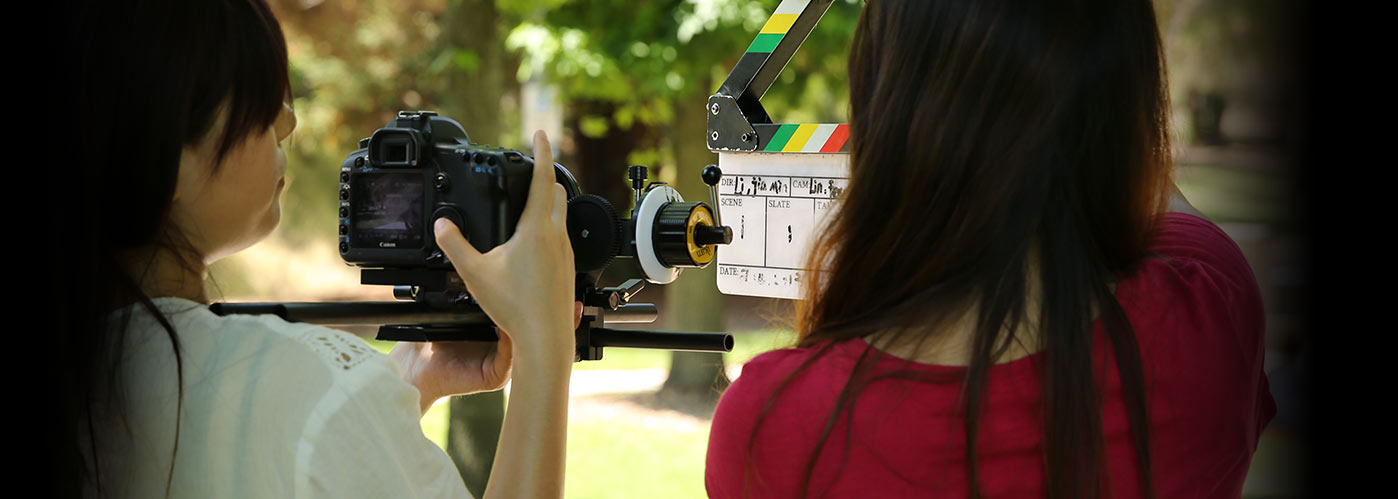 An over-the-shoulder view of two female NYFA students slating an outdoor shot.