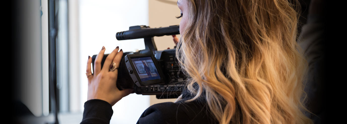A female NYFA student wearing rings watches the display screen of her camera while shooting on set.