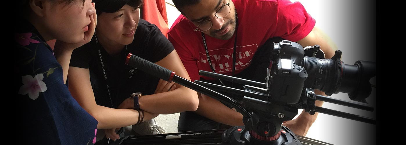 Three NYFA students peer together through at the display screen of a mounted camera.