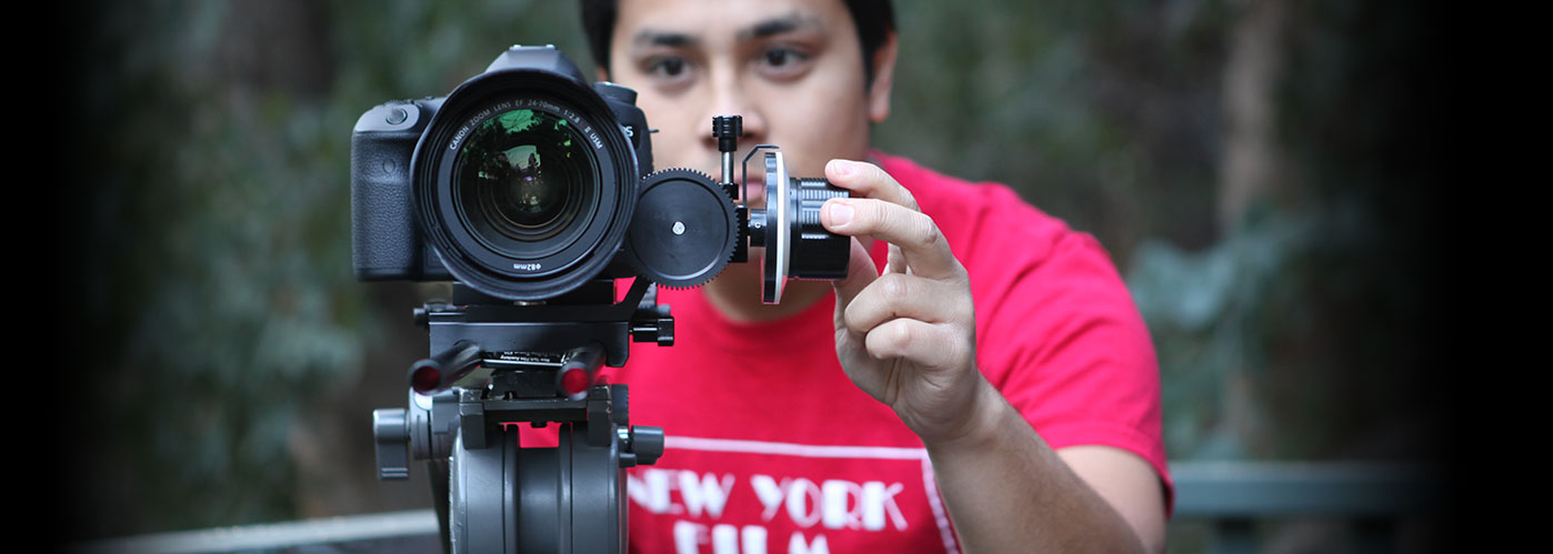 A New York Film Academy student points the camera directly at us,w with the lens in sharp focus.